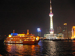 The Oriental Pearl Tower at night taken from the Bund. With a beautiful boat.
